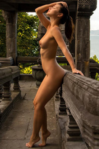Foxy petite brunette seductively poses naked in an ancient environment