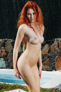 Redhead goddess Adel C flaunts her gorgeous pale body into a variety of poses