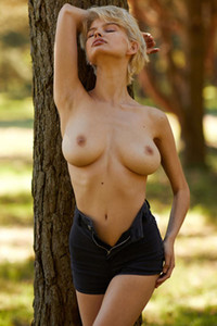 Busty blonde with juicy natural tits teasing in the middle of the park