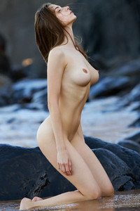 Big titted brunette already naked is playing and stretching on abandoned beach