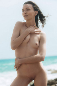 Small titted brunette Adel Morel looks so good while she is sunbathing on rock beach
