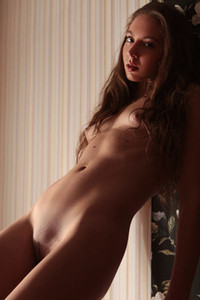 Foxy slender beauty Valery Leche seductively poses naked on the red sofa