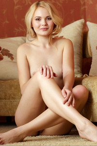 Blonde and adoring beauty exhibits her magnificent smile and her slender body on the sofa