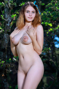 Angelic redhead babe Dakota Pink strips naked in the forest and squeezes her huge breasts