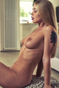 Stunning blonde strips off her white clothes and poses naked showing her perfect boobs