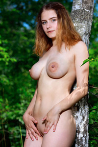 Redhead goddess with perfect pale and curvy body exposes her big boobs in nature