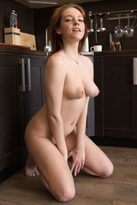 Gorgeous redhead doll playfully poses naked in the kitchen showing us her natural body