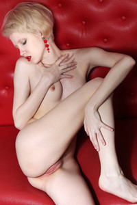 Shorthaired blondie Sindi seductively poses naked on the red leather sofa
