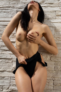 Dark haired goddess Clio slips out of her black bodysuit revealing astonishing body curves