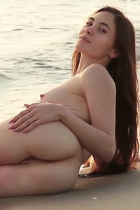 Brunette girl with nice natural body posing naked on the lonely beach