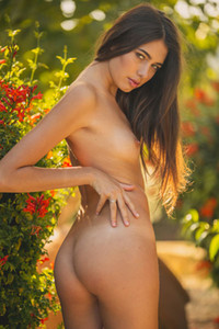 Delightful brunette hottie Katrine Pirs poses naked in the garden showing off her tanned body