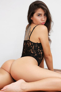 Beautiful brunette in transparent black bodysuit turns around showing us her big bouncing ass