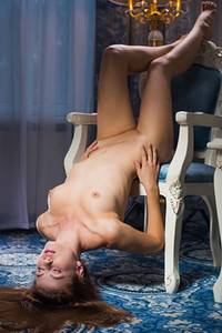 Irresistible long haired hottie Hilary C is on the chair stripping and posing for you