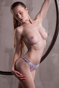 Well curved brunette doll Emily Bloom teasing on the large swinging metal ring