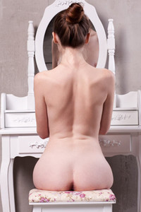 Brunette sweetheart Emily Bloom poses on the chair while baring her slender body with hot breasts