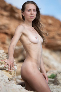 Attractive girl with amazing skinny body gets naked  and poses sensually on the rock