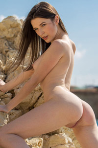 Superb girl is posing naked on the rock beach letting us see her bubble ass and small tits