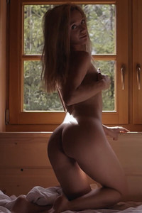 Blonde sweetheart shows off her seductive sexy body on the bed by the window