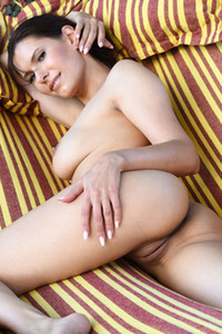 Dark haired goddess Susi R relaxes on the hammock presenting her tall tanned body