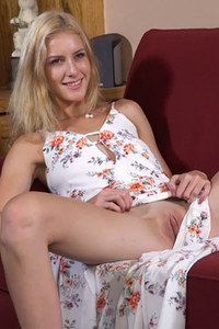 Slim blonde with long legs Mazzy Grace posing on the red couch for her photographer