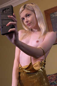 Young skinny blonde in golden dress taking selfies while showing her assets