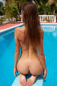 Skinny totally naked chick sensually poses on the poolside