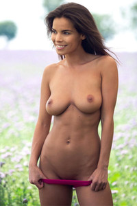 Natalie Costello a stunning brunette goddess delightfully poses in the outdoors in the meadow