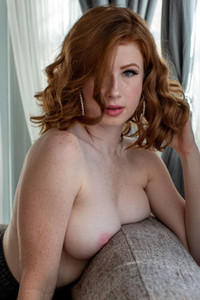 Magnificent redhead beauty gently strips and poses presenting her feminine curves