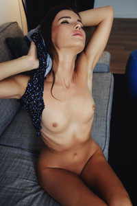 Incredibly sweet and sexy brunette spreads her legs to show us her shaved pussy on the sofa
