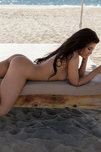 Stunning girl Carmen Nikole gets naked on the beach and starts rolling like that on the sunbed