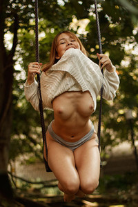Super sweet brunette is showing off her natural boobs and big white ass on the swing