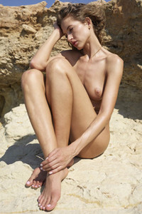 Seductive Taya strips naked on the rocks showing off her perfect body