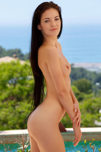 Beautiful longhaired brunette poses naked on the balcony showing us her nubile body