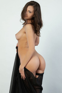 The astonishing brunette goddess takes off her long black gown showing us her perfect smooth body
