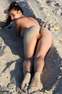 Medium titted Melissa is rolling naked in the sand showing off her stunning body