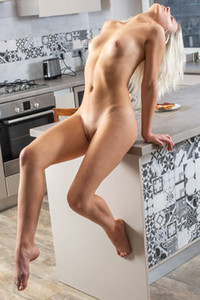 Perfect blondie Leaya poses naked in the kitchen and twists her smooth body
