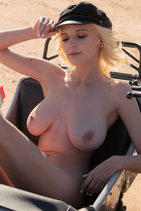 Blonde hottie Juniper Hope presents her huge boobs while she is posing on the motorcycle