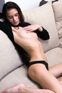 Sexy yet charming with stunning face sensually poses on the couch