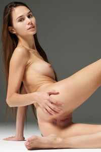 Beautiful brunette Leona stretches her pussy lips to show us her inner pinkness