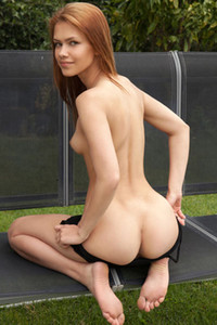 Tempting young doll Laina poses naked in the garden baring her nubile body