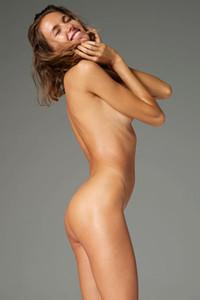 Perfectly shaped brunette Alya poses naked baring her oiled slender body