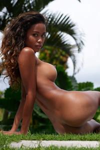 Exotic ebony honey seductively poses naked by the tropical pool