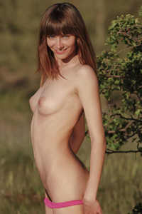 Sweet and petite brunette playfully poses naked in nature