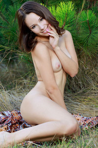Angelic brunette honey Emmy poses naked in nature baring her pale body