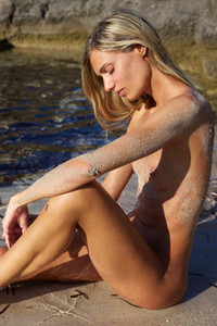 Slender beauty poses naked on the beach with her smooth skin covered with sand