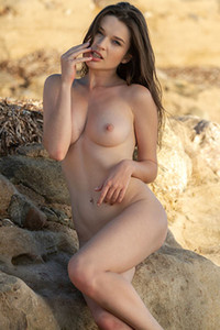 The sweet young model leaves us breathless with seductive naked posing on the beach