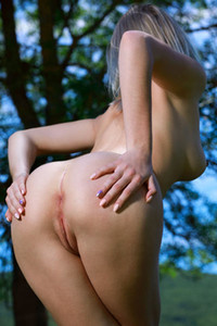 Young cutie teasing with her nubile body as she poses outdoors in nature