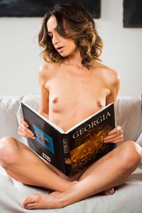 Gorgeous foxy doll poses naked on the sofa as she reads a book