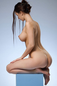 Charming doll with beautiful breasts poses naked for the camera objective