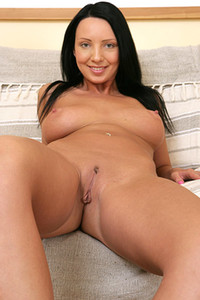 Foxy vixen stuffing both of her love holes with an orange dildo in the living room